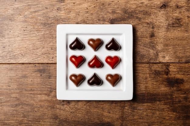 Czekoladowi cukierki na bielu talerzu na drewnie