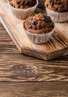 Czekoladowi muffins na drewnianej deski wysokim widoku