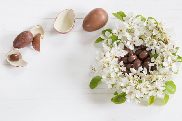 Czekoladowi wielkanocni jajka z wiosną kwitną na drewnianym tle