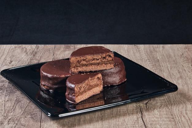 Czekoladowy alfajor na czarnym talerzu na drewnianym stole i ciemnym tle. selektywna ostrość. skopiuj miejsce