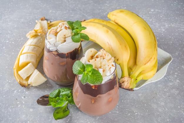 Czekoladowy budyń bananowy, warstwowy deser w szklance z plastrami banana i polewą czekoladową. pyszny wegański mus czekoladowy z bananem, kakao i orzechami
