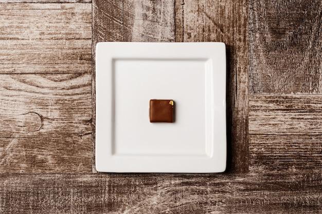 Czekoladowy cukierek na bielu talerzu na drewnianym