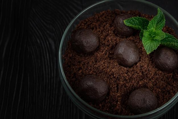 Czekoladowy deser ciasteczka z kawałkami czekolady i miętą na ciemnym drewnianym tle z...