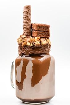 Czekoladowy ekstremalny koktajl mleczny z ciastem brownie, pastą czekoladową i słodyczami. szalony, dziwaczny trend żywieniowy. skopiuj miejsce