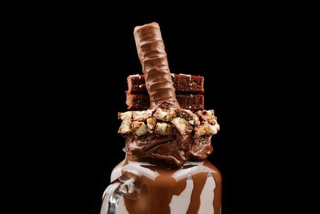 Czekoladowy ekstremalny koktajl mleczny z ciastem brownie, pastą czekoladową i słodyczami.