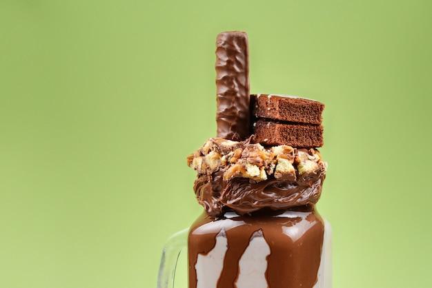 Czekoladowy ekstremalny koktajl mleczny z ciastem brownie, pastą czekoladową i słodyczami