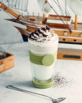 Czekoladowy koktajl mleczny w szkle zwieńczony bitą śmietaną i czekoladą