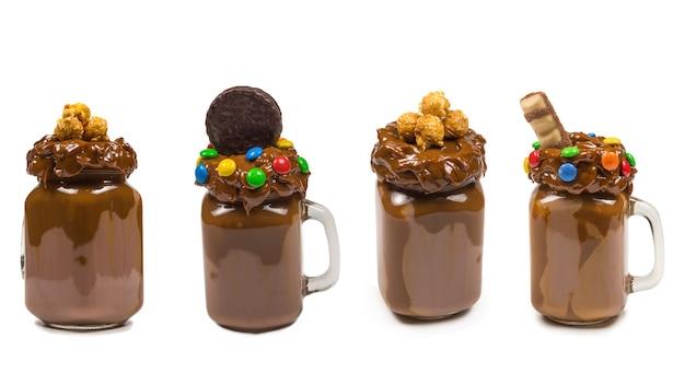 Czekoladowy koktajl mleczny z bitą śmietaną, ciasteczkami, goframi, podawany w szklanym słoiku mason. słodki koktajl