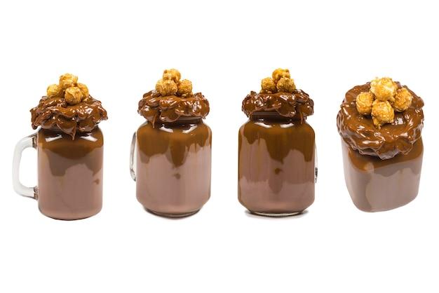 Czekoladowy koktajl mleczny z bitą śmietaną, ciasteczkami, goframi, podawany w szklanym słoiku. słodki shake