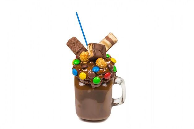 """Czekoladowy koktajl mleczny z bitą śmietaną, ciastkami, goframi, podawany w szklanym słoiku z kamienia. słodki shake """"freak or crazy"""". odosobniony."""