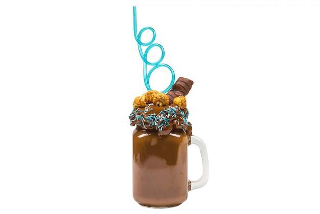 """Czekoladowy koktajl mleczny z bitą śmietaną, ciastkami, goframi, podawany w szklanym słoiku z masonem. słodki shake """"freak or crazy"""". odosobniony."""