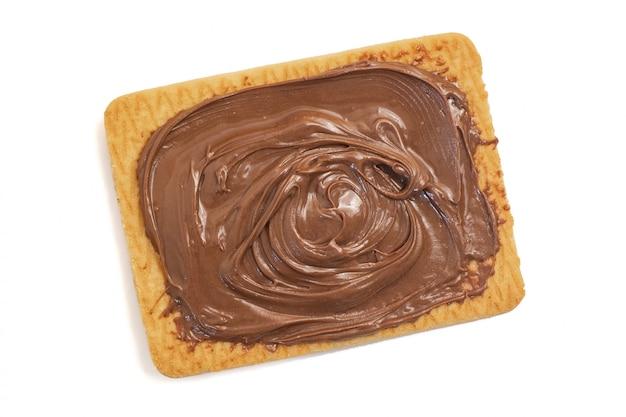 Czekoladowy krem z orzechów laskowych na plik cookie na białym tle. widok z góry. ścieśniać