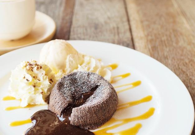 Czekoladowy lawa tort w bielu talerzu z filiżanką na starym drewnianym stole