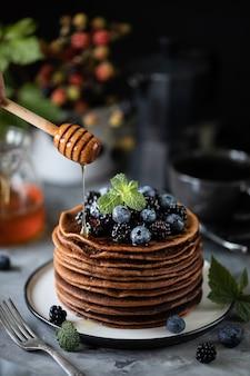 Czekoladowy naleśnik z jagodami i owocami z miodem, z latającym cukrem pudrem i bukietem dzikich kwiatów na stole. ciemny