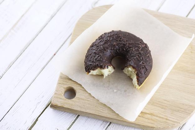 Czekoladowy pączek na drewnianym białym tle i rozrzucone słodkie ozdoby