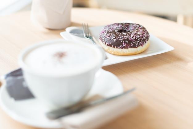 Czekoladowy pączek z filiżanką kawy na stole