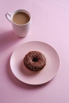 Czekoladowy pączek z posypką na talerzu w pobliżu filiżanki kawy, słodkie glazurowane jedzenie deserowe i gorący napój na różowym minimalnym stole, widok pod kątem