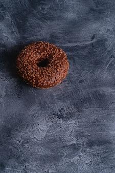 Czekoladowy pączek z posypką, słodkie glazurowane jedzenie deserowe na ciemnym betonie teksturowanym, miejsce kopiowania kąta widzenia