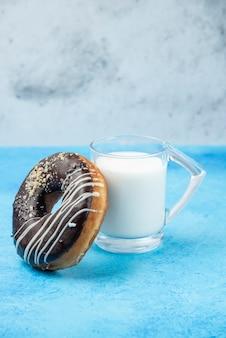 Czekoladowy pączek ze szklanką mleka na niebieskim stole.