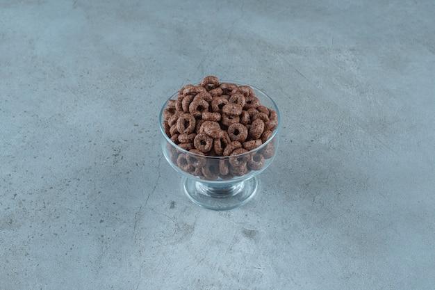 Czekoladowy pierścionek kukurydziany w szklanym cokole, na niebieskim tle. zdjęcie wysokiej jakości