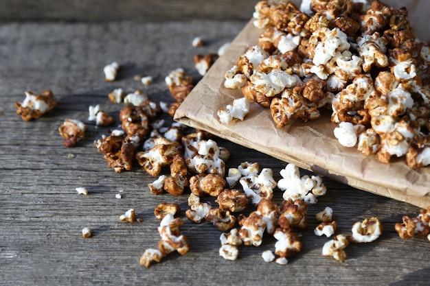 Czekoladowy popcorn wysypuje się z papierowej torby