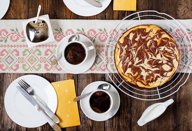 Czekoladowy sernik i kawa na drewnianym stole. filiżanka kawy i sernik. widok z góry leżał płasko