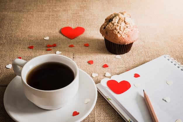 Czekoladowy słodka bułeczka i kawa i serca na parciakowych teksturach