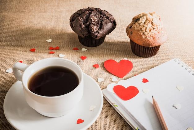 Czekoladowy słodka bułeczka, kawa i serca na parciakowych teksturach