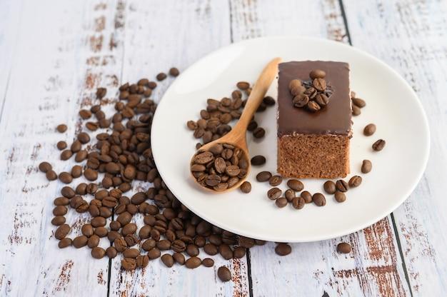 Czekoladowy tort na białym talerzu i kawowe fasole na drewnianej łyżce na drewnianym stole.