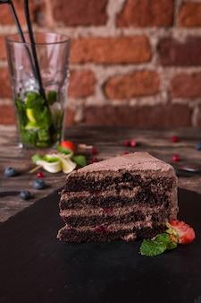Czekoladowy tort na kamiennym talerzu na nieociosanym drewno stole