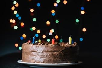 Czekoladowy tort przeciw błyskotliwości bokeh zaświeca czarnego tło