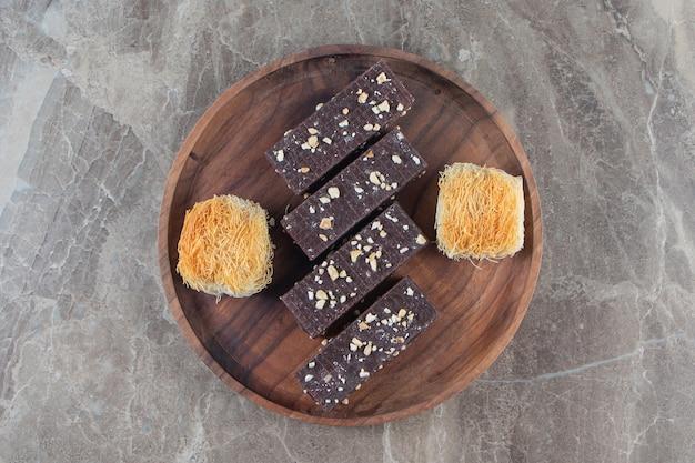 Czekoladowy wafel i kadayif na drewnianym talerzu na marmurze.