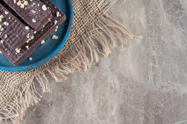 Czekoladowy wafel na drewnianym talerzu na fakturze na marmurze.