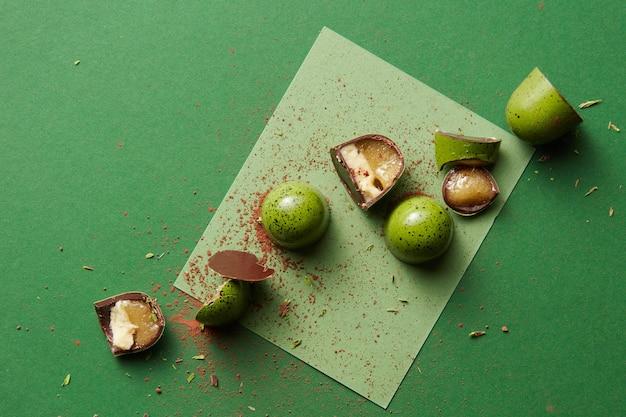 Czekoladowy zielony cukierek z galaretką na zielonym tle