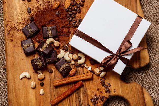 Czekoladowych cukierków cynamon i dokrętki na drewnianym biurku.