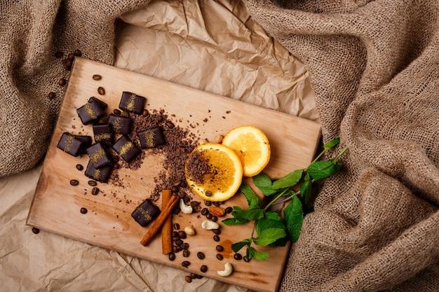 Czekoladowych cukierków pomarańczowy miętowy cynamon i dokrętki na drewnianym biurku.