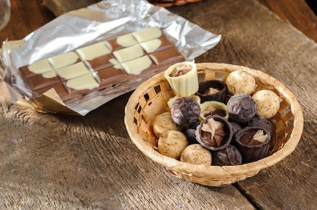 Czekolady i czekolada w koszu na drewnianym stole