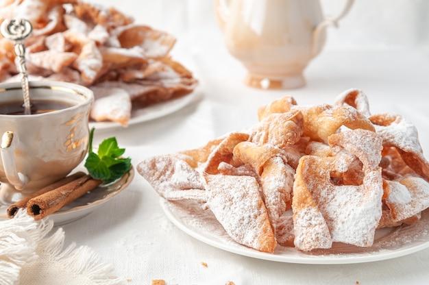 Czenchi karnawałowe słodycze na białym talerzu posypane cukrem pudrem w pobliżu znajduje się filiżanka herbaty ozdobiona cynamonem i miętą białe tło zbliżenie