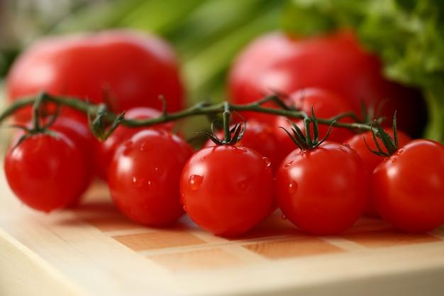 Czereśniowi pomidory kłamają na tnącej desce w kuchni przeciw tłu zieleni zdrowego łasowania pojęcie