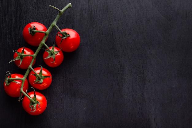 Czereśniowi pomidory na czarnym drewnianym stole. skopiuj miejsce tło dla kawiarni, menu, książka kucharska dla przepisów kulinarnych, restauracja.