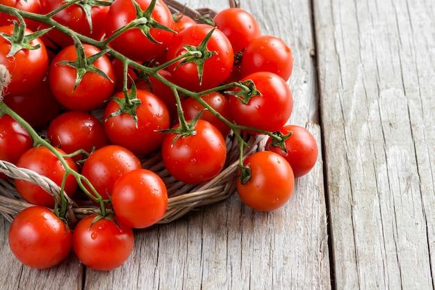 Czereśniowi pomidory na drewnianym tle