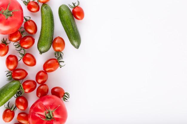 Czereśniowych pomidorów czerwony świeży dojrzały z czerwonymi pomidorami i zielonymi ogórkami na białym tle