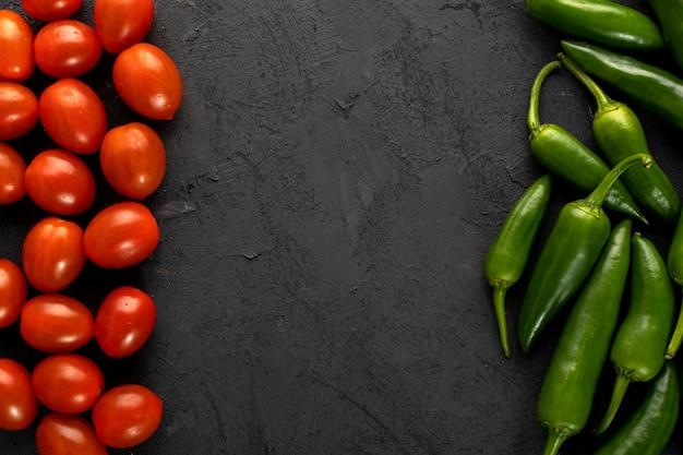 Czereśniowych pomidorów czerwony świeży i zielony korzenny pieprz na ciemnym tle