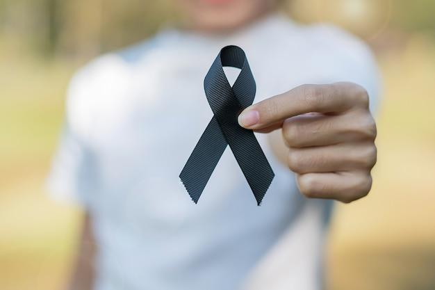 Czerniak i rak skóry, miesiąc świadomości obrażeń wywołanych szczepieniami i koncepcje odpoczynku w pokoju. kobieta trzyma czarną wstążkę