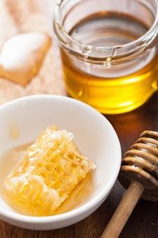 Czerpak o strukturze plastra miodu i miód w słoiku na drewnianym stole