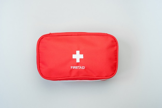 Czerwona apteczka pierwszej pomocy torba na szarym tle. koncepcja ratownictwa medycznego.