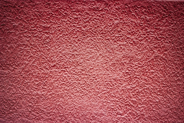 Czerwona betonowa ściana w tle w kolorze cementu, abstrakcyjna struktura budynku .