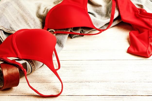Czerwona bielizna i dżinsy rozrzucone na podłodze. niechlujne ubrania