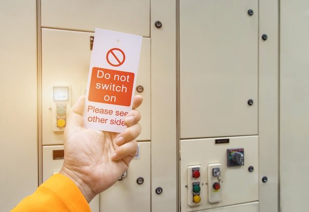 Czerwona blokada klucza i znacznik w dłoni do odcięcia procesu elektrycznego, numer przełącznika do oznaczenia wylogowania elektrycznego.