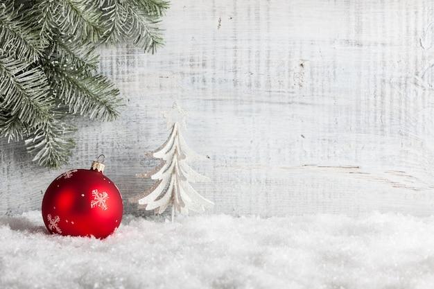 Czerwona bombka na śniegu i drewnianym tle